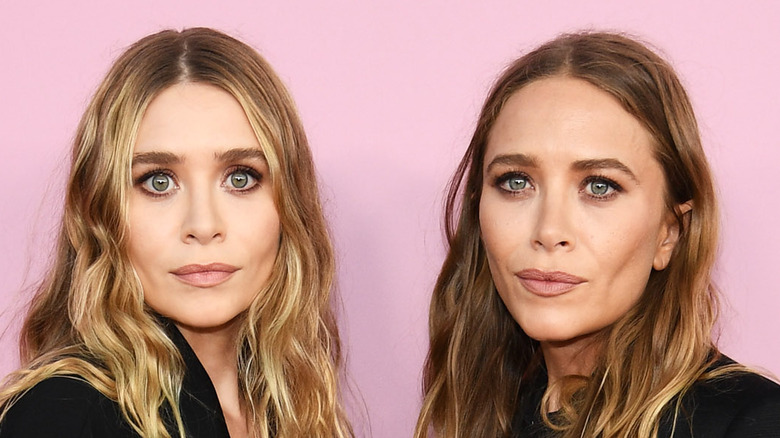 Mary-Kate and Ashley Olsen pose together at an event