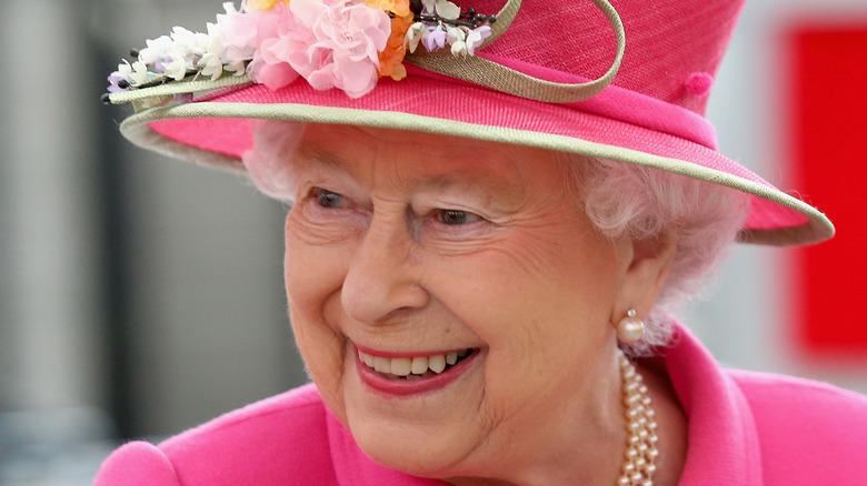 Queen Elizabeth smiles in a pink hat
