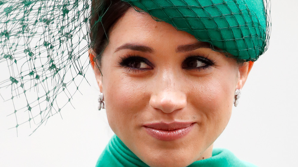 Meghan Markle wears a green hat with mesh