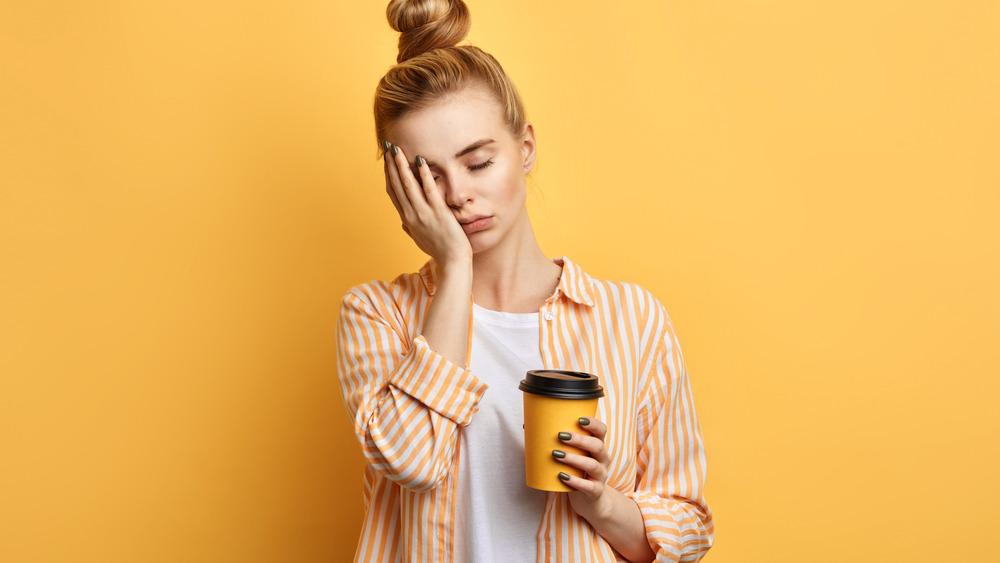 Sad woman holding coffee cup