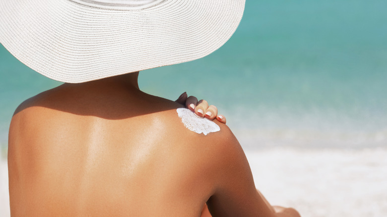 Woman applying sunscreen to her back