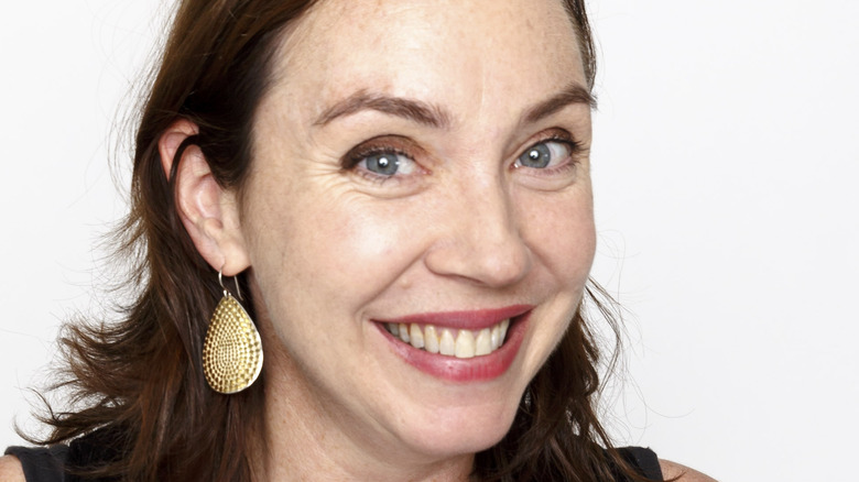 Stephanie Courtney poses in front of a white background with a big smile.