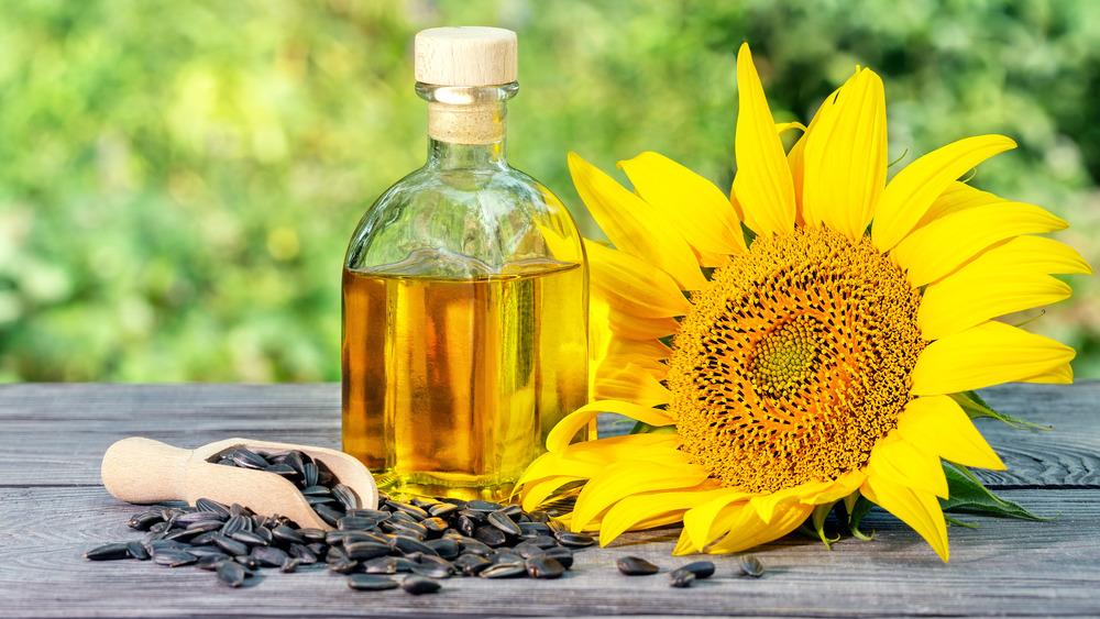 a sunflower, sunflower seeds, and a glass bottle of sunflower oil