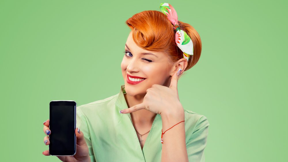 Woman making retro phone hand gesture