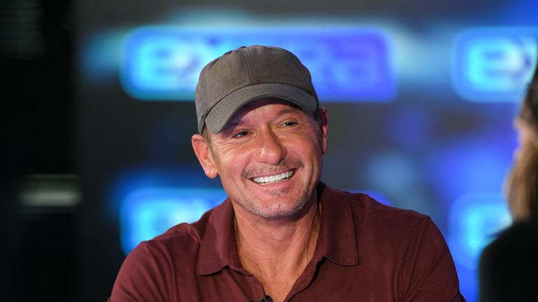 Tim McGraw smiling in baseball cap