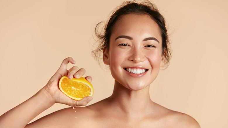 Woman holding orange for skincare