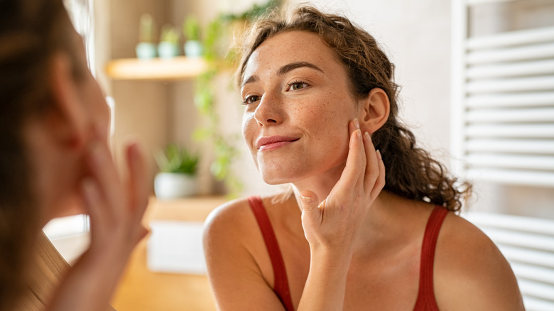 Woman touching skin, looking in mirror