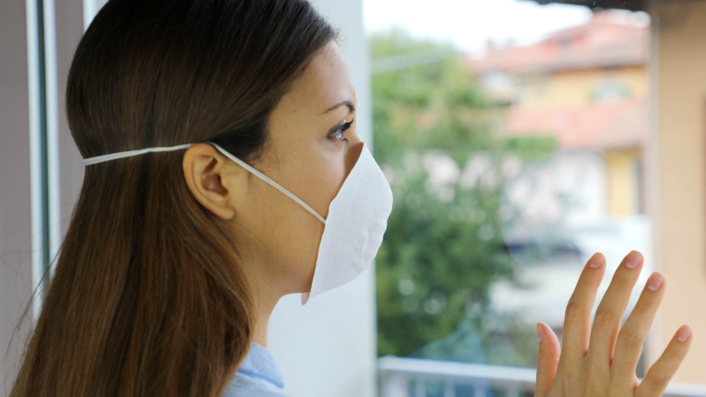 Woman wearing face mask looking out window