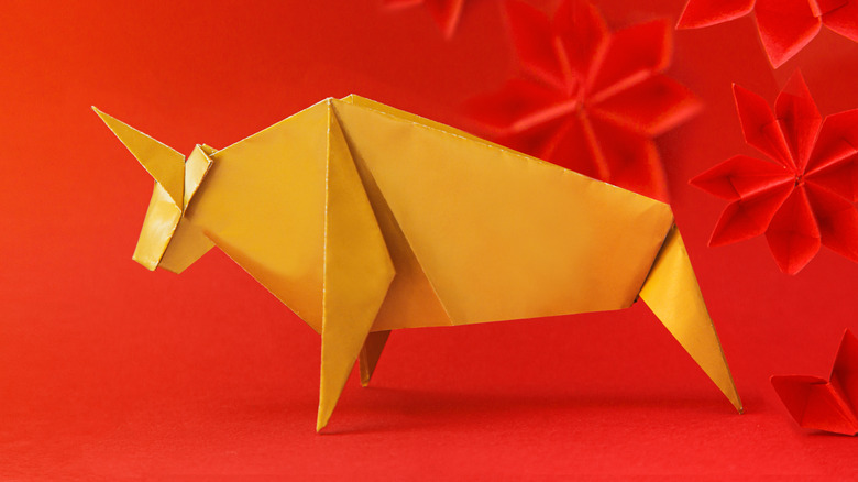 Origami animal in front of red background