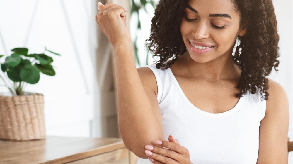 Woman moisturizing her elbow