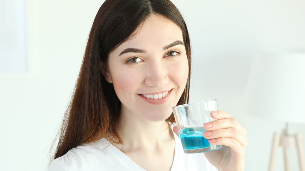A smiling woman holding a glass of mouthwash