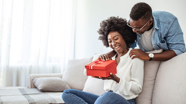 Couple laughing, opening gift
