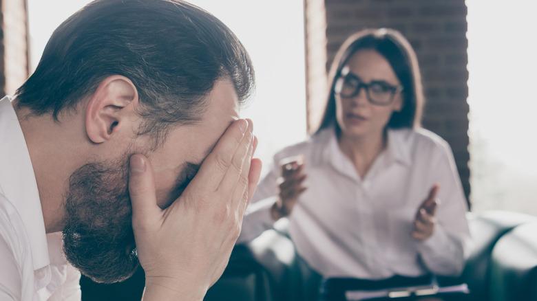 Woman speaking to visually upset man