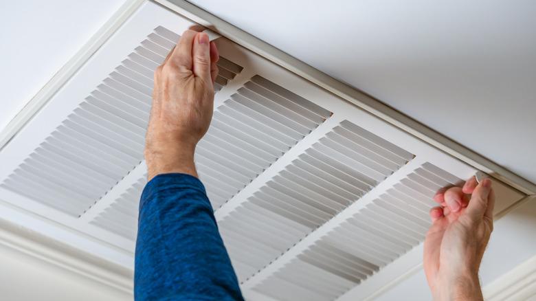 Man opening an air vent