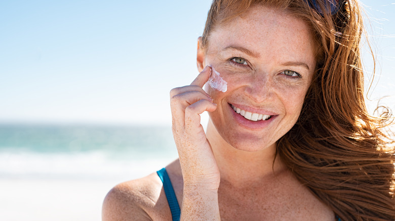 woman applying sunscreen and smiling