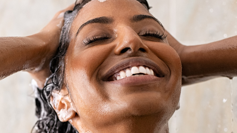 A smiling woman washes her hair in the shower.