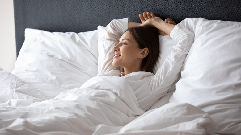 Woman waking up in a comfy, plush bed