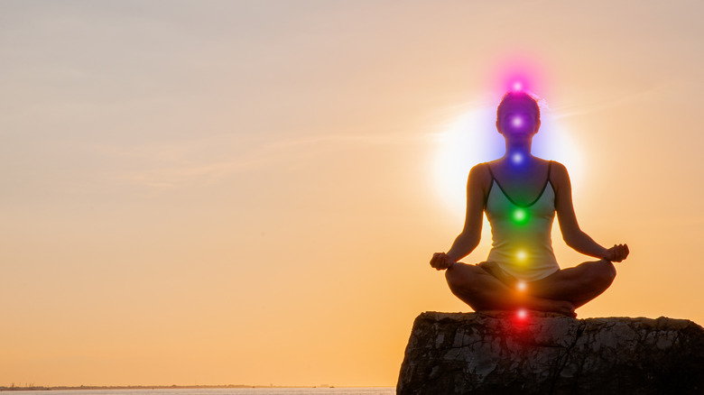 A person meditating with their chakras lit up