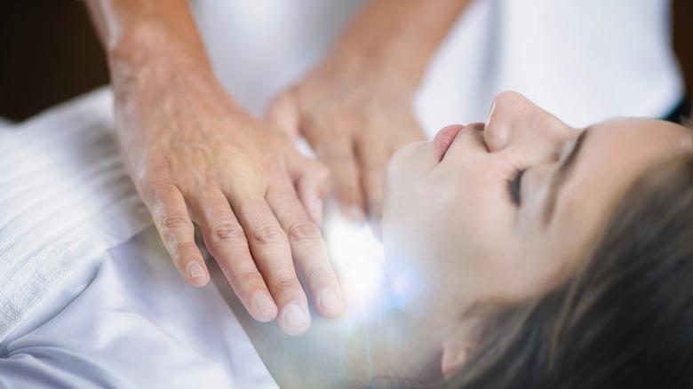 Person healing woman's throat chakra