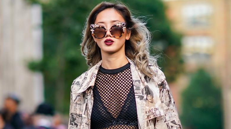Woman wears black bra under black mesh shirt