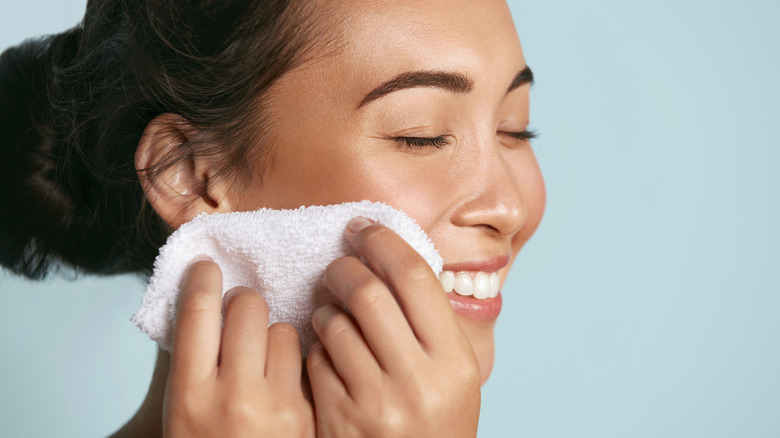 A woman using a soft cloth on her face