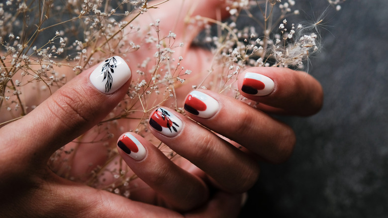 Hand with painted nails holding flowers
