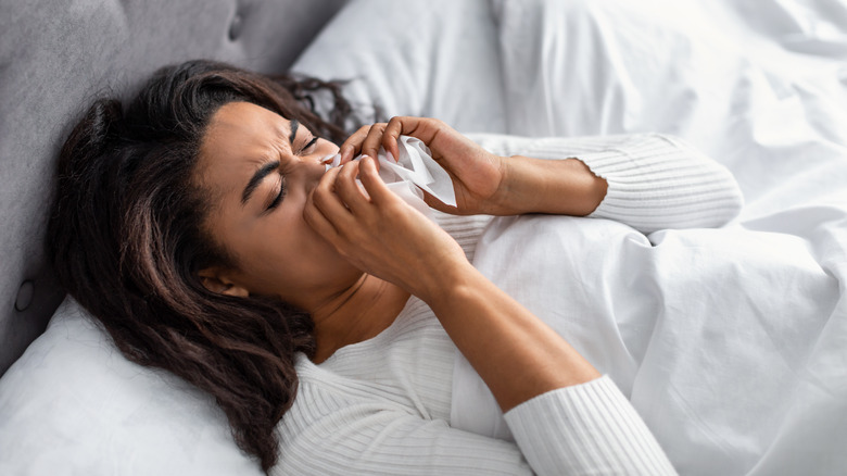 woman suffering from running stuffy nose and sore throat in bed