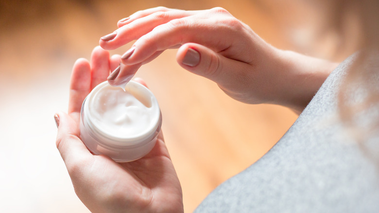 Woman with lotion on fingers