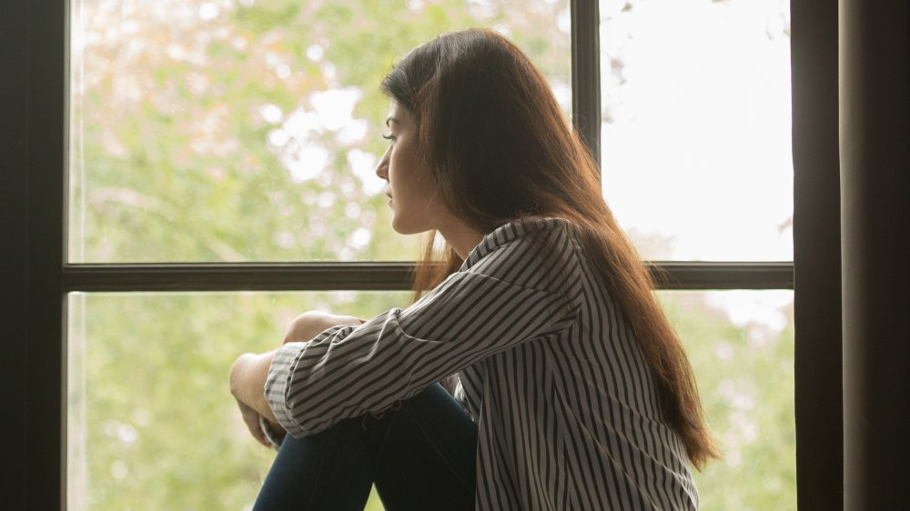 lonely woman sitting by a window
