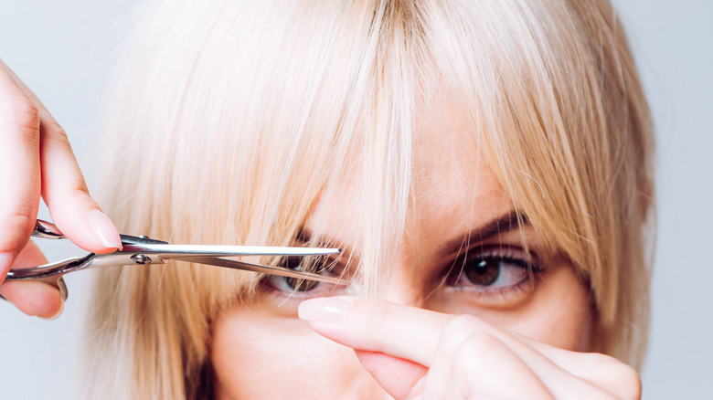 Blonde woman holding pair of scissors to her bangs