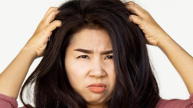 Brunette woman scratching her scalp