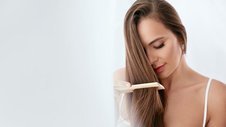 Woman combing through long brown hair