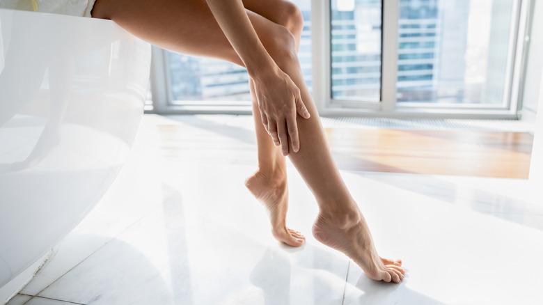 Woman applying body oil to her legs