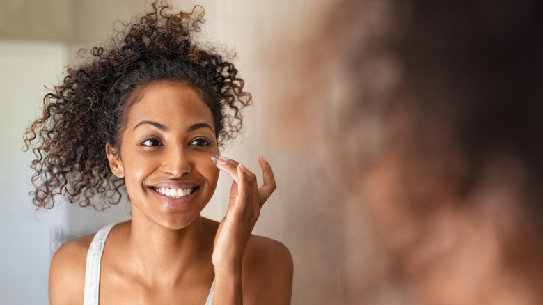 Woman smiling and applying moisturizer