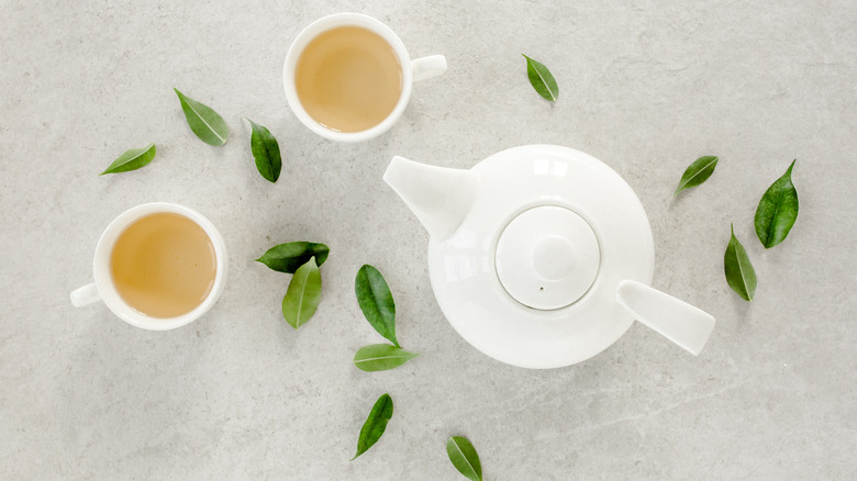A teapot with teacups and leaves