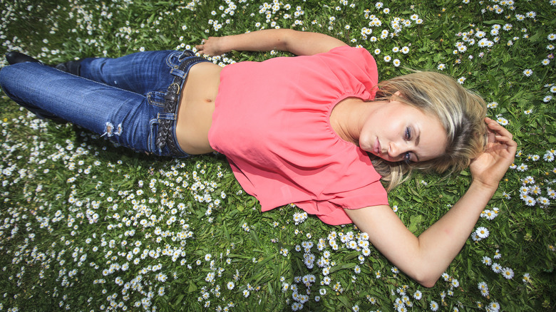 Woman lying in grass wearing low-rise jeans