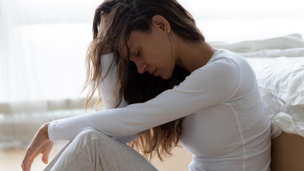 Worried woman sitting beside bed