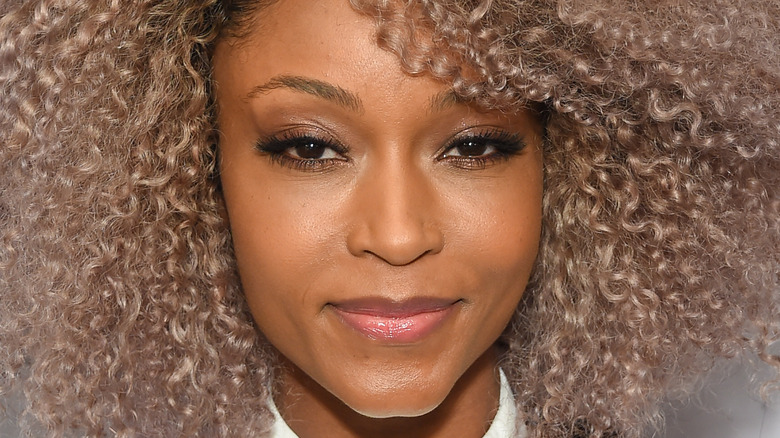 Yaya DaCosta smiles with her hair curled and dark eye makeup.