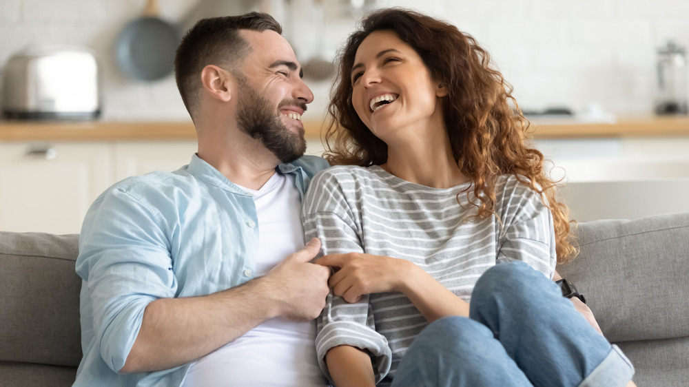 Couple laughs together on the couch