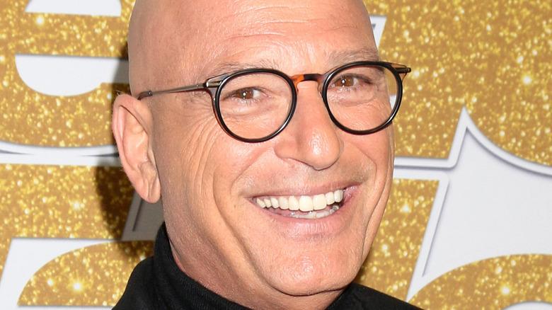 Howie Mandel smiles with black framed glasses.