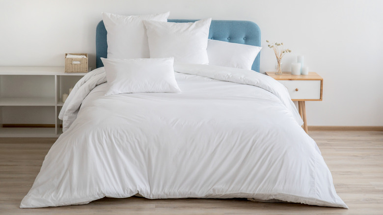 A bed with all-white bedding.