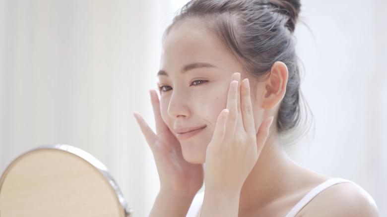 woman skin care rubs face