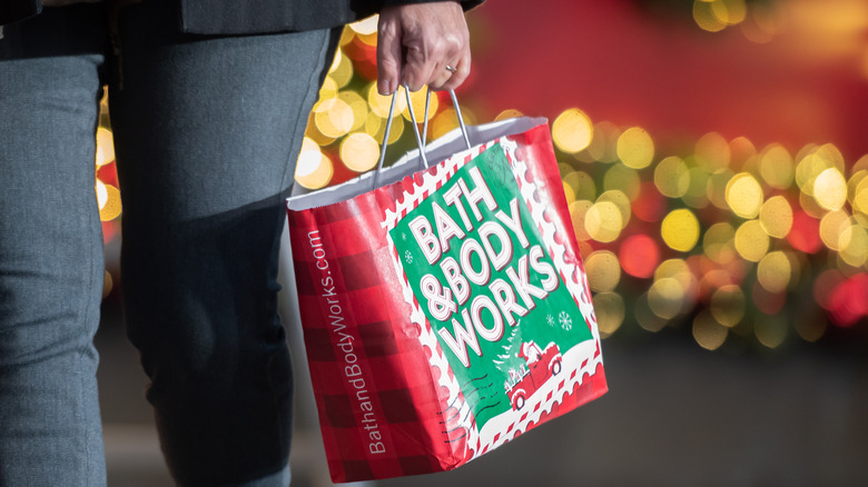 Woman carrying holiday-themed Bath & Body Works bag