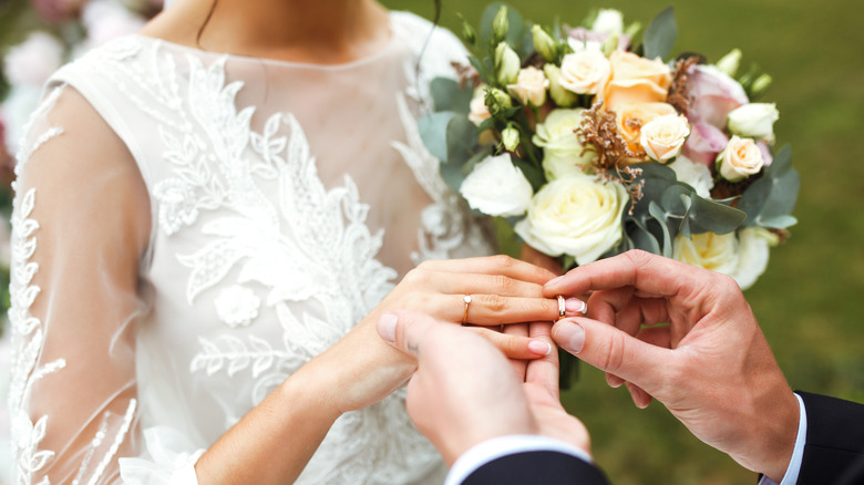 husband putting wedding ring on wife