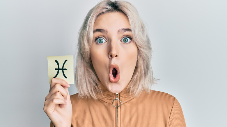 Surprised-looking woman holding Pisces symbol