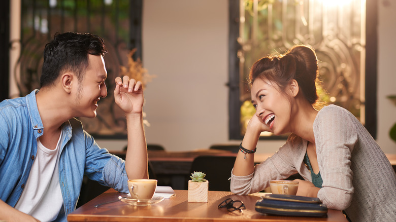 Couple on a first date laughing over coffee