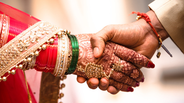 Indian bride and groom hold hands