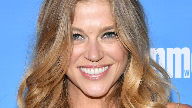 Adrianne Palicki smiles with wavy hair and blue eyeshadow