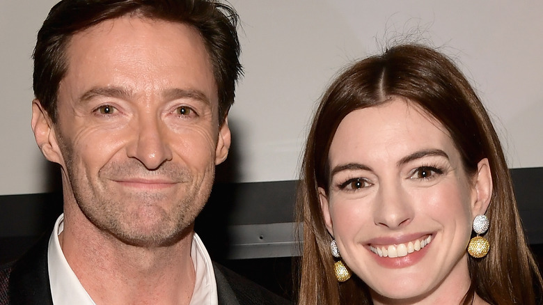 Anne Hathaway and Hugh Jackman smile for the camera at an event