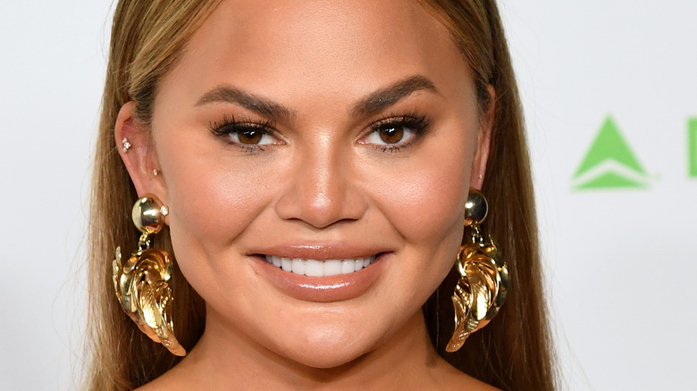 Chrissy Teigen smiling with large gold earrings